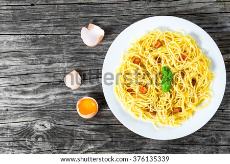 Spaghetti carbonara on a white dish with basil leaves, eggs yolk, grated parmesan cheese and bacon, freshly ground black pepper, traditional Italian recipe, close-up - stock photo