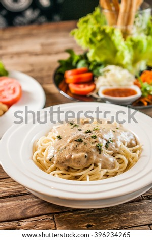 Spaghetti Carbonara on white plate over wooden table - stock photo