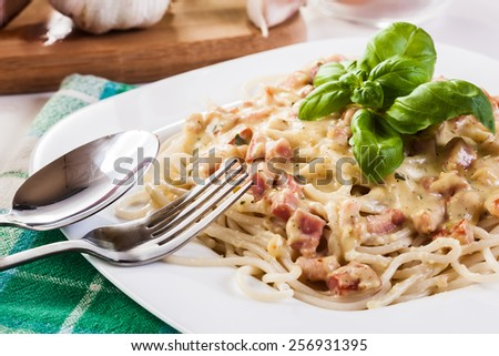 Spaghetti carbonara with bacon and basil on a plate - stock photo