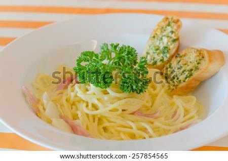 Spaghetti Carbonara with bacon and garlic bread on dish - stock photo