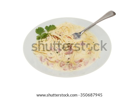 Spaghetti carbonara with coriander leaves and a fork in a bowl isolated against white - stock photo