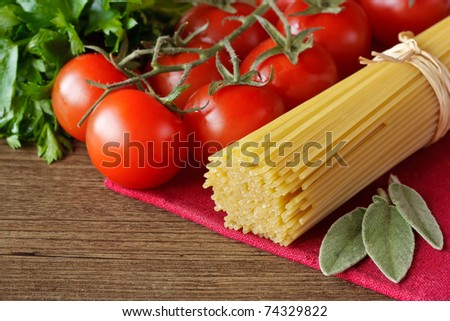 Spaghetti, cherry tomatoes and parsley on a wooden table. - stock photo