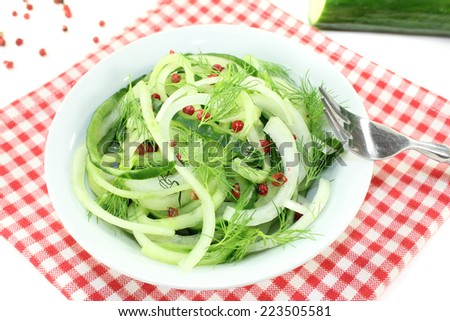Spaghetti cucumber with red pepper and onions on bright background