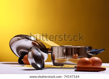 spaghetti, eggs, cheese and utensils on table