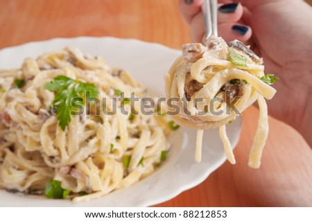 Fettuccine carbonara in a white bowl, garnished with bacon, mushrooms ...