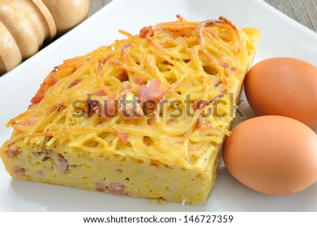 spaghetti frittata with eggs cheese and bacon then fried in a pan - stock photo