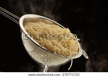 Spaghetti in a collander isolated on black background  - stock photo