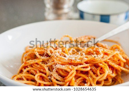 Spaghetti in a tomato sauce, topped with parmesan cheese
