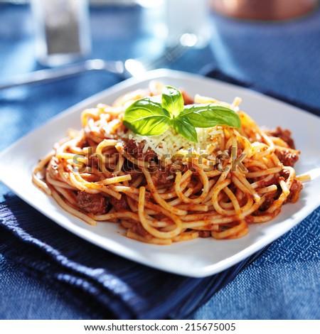 spaghetti in bolognese sauce with basil garnish - stock photo
