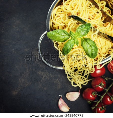 spaghetti in colander on dark vintage background - stock photo