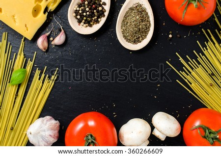 Spaghetti ingredients over dark background - stock photo
