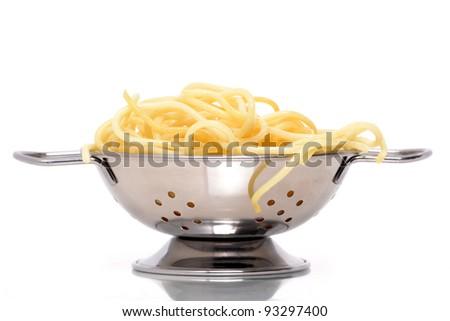 spaghetti noodles in colander white background - stock photo