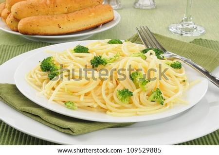 Spaghetti noodles with garlic butter, broccoli and bread sticks - stock photo