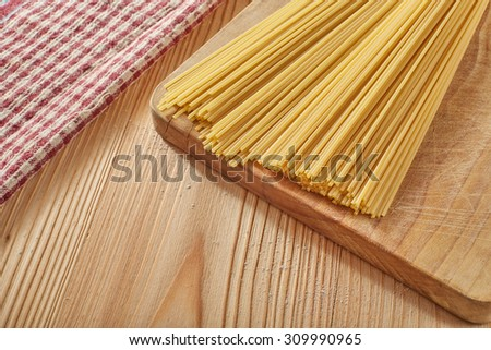 Spaghetti on a cutting board on a wood table with a napkin in the corner with some flour around - stock photo