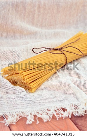 Spaghetti on a wooden table, which is laid out with a cloth