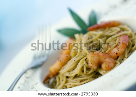 Spaghetti (pasta) and prawns in cream sauce, herb garnish. On deep white, round bowl, wide rim sprinkled with ground pepper. Angled, landscape, shallow depth of field, focus on prawns near front.