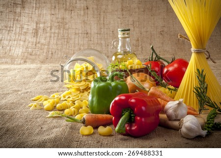 Spaghetti, pasta, vegetables and spices on sackcloth. - stock photo