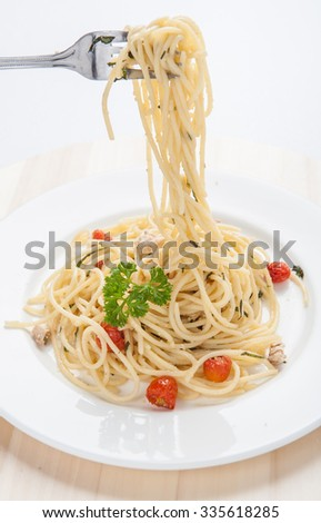Spaghetti pasta with cherry tomatoes, basil and parmesan cheese, selective focus