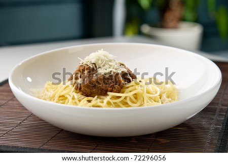 Spaghetti pasta with meat and cheese on the table in restaurant - stock photo
