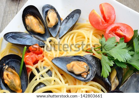 spaghetti pasta with mussels with fresh tomato olive oil and parsley - stock photo