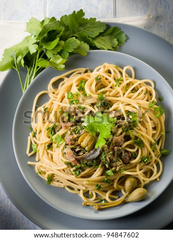 spaghetti with anchovies parsley and capers - stock photo