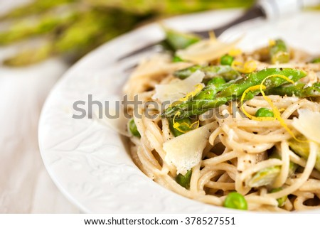 Spaghetti with asparagus and green peas - stock photo
