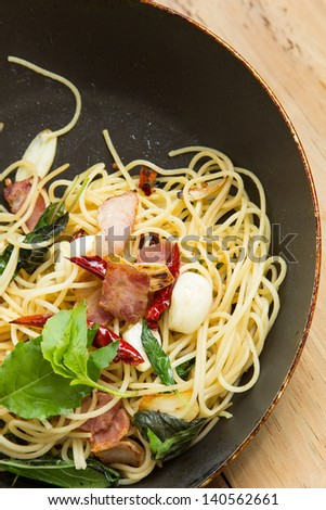 spaghetti with bacon in the pan and herb