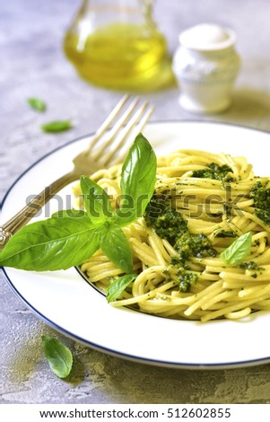 Spaghetti with basil pesto on a white plate on a grey concrete or stone background.