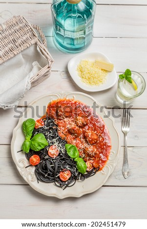 Spaghetti with black pasta, meatballs and cheese