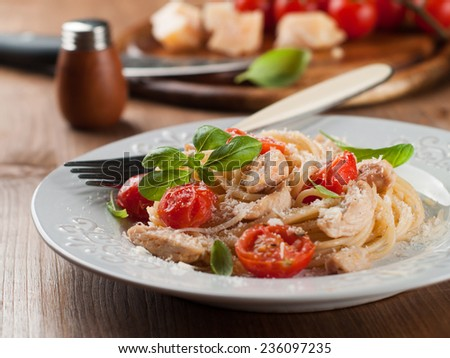 Spaghetti with chicken, cherry tomato and cheese, selective focus - stock photo