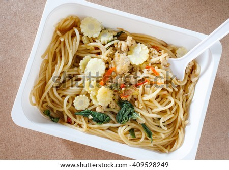Spaghetti with chili pork basil leaf in food container on wood background.Top view.
