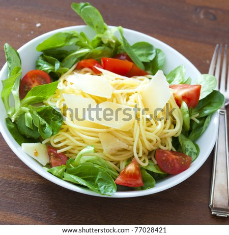 Spaghetti with field salad, tomatoes and parmesan