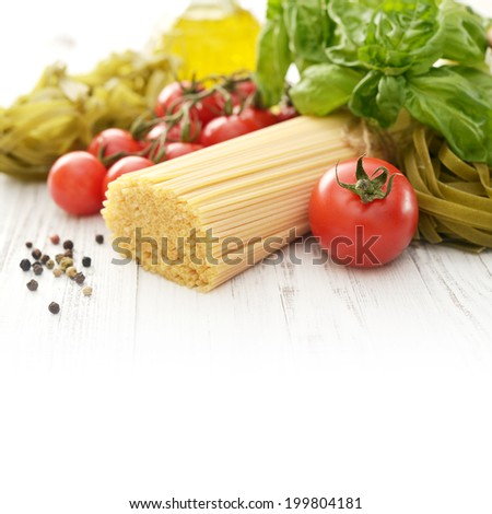 Spaghetti with fresh ripe tomato and basil on wooden background with copy space