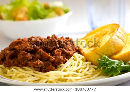 Spaghetti with garlic bread sitting next to it with a salad and a glass of water in the background.