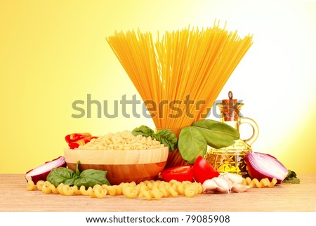 spaghetti with garlic, onion, spices  and basil on a yellow background - stock photo