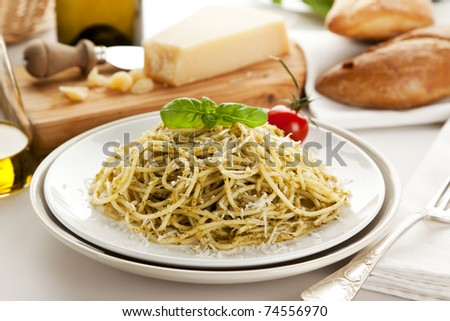Spaghetti with Genovese pesto sauce, garnished with basil leaf and tomato, parmesan cheese and bread in background - stock photo