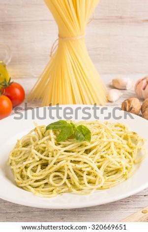 spaghetti with green pesto sauce with ingredients - stock photo