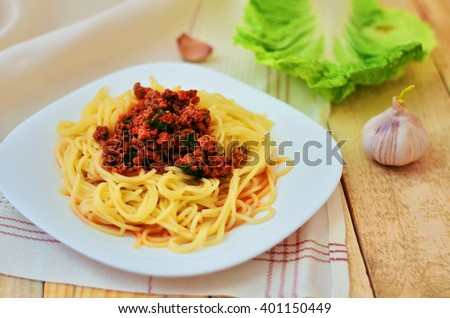 Spaghetti with meat in tomato sauce on a white plate. A plate of spaghetti on a napkin on a wooden background - stock photo