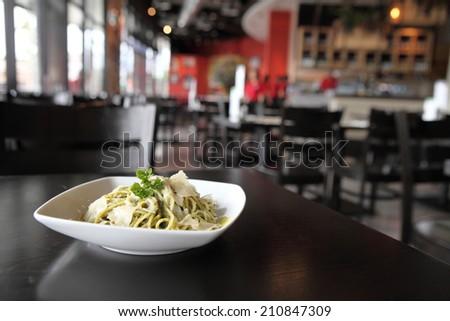 spaghetti with pesto sauce on wood background - stock photo