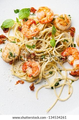 Spaghetti with prawns, sea scallops and basil - stock photo