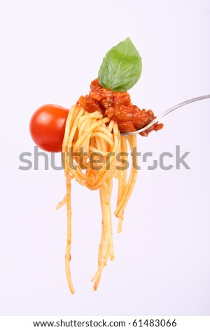 Spaghetti with sauce bolognese hanging on a fork with a cherry tomato,  decorated with fresh basil - stock photo