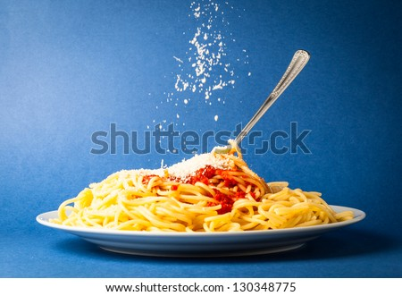Spaghetti with simple tomato and falling Parmesan cheese on a blue background - stock photo