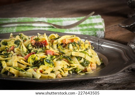 Spaghetti with spinach and bacon on a wooden table. Selective focus. - stock photo