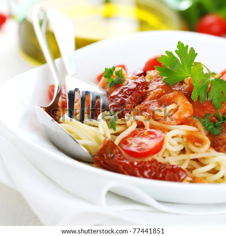 Spaghetti with sun dried tomatoes and tomato sauce on white plate - stock photo