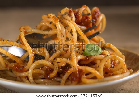 Spaghetti with tomato sauce and fork close up - stock photo