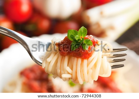 Spaghetti with tomato sauce and ingredients. Cherry tomatoes, onions, garlic and oregano. - stock photo