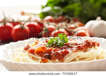 Spaghetti with tomato sauce and ingredients. Cherry tomatoes, onions, garlic and parsley. - stock photo