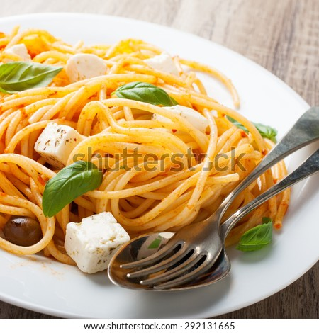 Spaghetti with tomato sauce, feta cheese and basil leaves on white plate on wooden background. Italian healthy food background. - stock photo