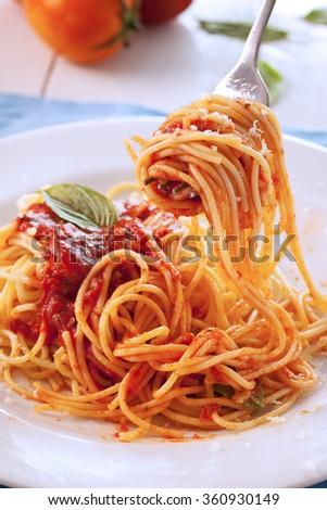 spaghetti with tomato sauce on fork - stock photo