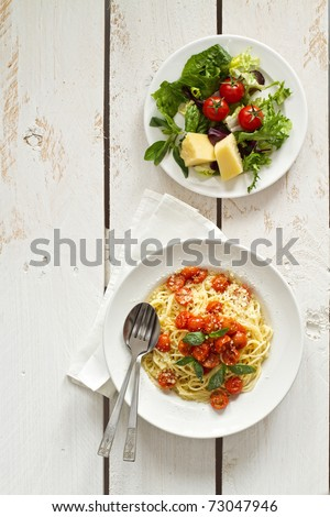 Spaghetti with tomato sauce on white wooden background - stock photo